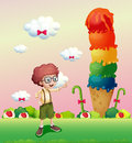 A young gentleman standing near the giant icecream illustration of Stock Photo