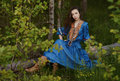 Young gipsy in the forest blue dress at Royalty Free Stock Photos
