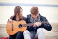 Young girl with acoustic guitar and her boyfriend on the bach Stock Images