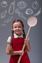 Young girl with apron and large wooden spoon vegetables healthy eating concept Royalty Free Stock Image