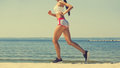 Young girl athlete, in shorts and top running on the beach in summer, morning exercise. Royalty Free Stock Photo