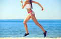 Young girl athlete, in shorts and top running on the beach in summer, morning exercise Royalty Free Stock Photo