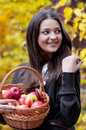 Young girl in autumn park with a basket of apples beautifulgirl Royalty Free Stock Image