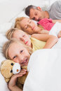 Young girl awake next to her sleeping family in bed Royalty Free Stock Photos