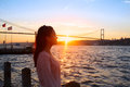 Young girl on background of Bosphorus bridge and sunset Royalty Free Stock Photo