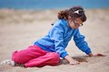 Young girl on beach one wearing a blue fleece jumper and pink trousers sits alone a looking down at the sand Royalty Free Stock Photography