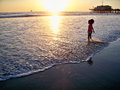 Young girl at the beach santa monica by pier beautiful sunset and sailboats in horizon s feet are in water Royalty Free Stock Photos