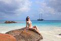 Young girl on the beach of seychelles sitting big rock Royalty Free Stock Images