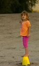 Young girl at beach standing on buckets Royalty Free Stock Photo