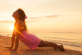 Young girl on beach at sunrise doing yoga exercise Royalty Free Stock Photo
