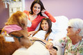 Young girl being visited in hospital by therapy dog lying bed smiling with mom and volunteer beside Royalty Free Stock Images