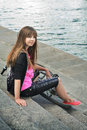 Young girl with bicycle sitting on the steps of the waterfront Royalty Free Stock Photo