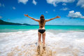 Young girl in bikini with raised arms greeting tropical sea and sun, on beach, freedom, vacation