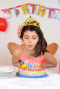 Young girl blowing birthday candles Royalty Free Stock Images