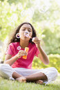 Young girl blowing bubbles outdoors Royalty Free Stock Images