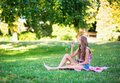 Young girl blowing bubbles sitting on the grass and Royalty Free Stock Photos