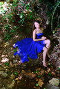 A young girl in a blue dress at the creek beautiful evening near water Royalty Free Stock Photo