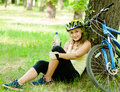 Young girl with a bottle water in his hand is resting after biking Royalty Free Stock Photo