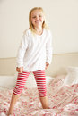 Young Girl Bouncing On Bed Stock Images