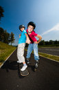 Young girl boy roller skating skateboarding Stock Image