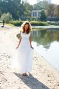 Young girl bride walk barefoot the sunny coast of the river in a white dress outdoor Stock Image