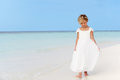 Young girl bridesmaid dress walking beautiful beach sun Royalty Free Stock Photos