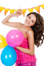 Young girl with bright colored balloons on a white and cake Royalty Free Stock Images