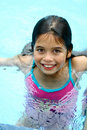A young girl with brown eyes enjoys being in the swimming pool