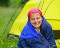 Young girl camping in a sleeping bag near tent in on the nature Royalty Free Stock Photography