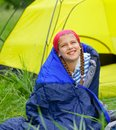 Young girl camping in a sleeping bag near tent in on the nature Royalty Free Stock Photos