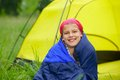 Young girl camping in a sleeping bag near tent in on the nature Stock Photography