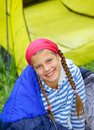 Young girl camping in a sleeping bag near tent in on the nature Royalty Free Stock Image