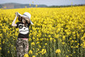 Young girl in canola field with sunhat rapeseed crop Royalty Free Stock Image