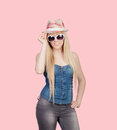 Young girl with a cap and sunglasses on over pink background Royalty Free Stock Image