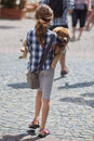 Young girl carries her puppy in the city Stock Images