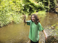 Young girl catches small trout photo of holding up while fishing on a stream Stock Photography