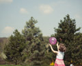 Young girl catching purple ball in park Royalty Free Stock Photo