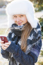 Young girl with cell phone in winter portrait of teenage holding mobile outside Stock Image