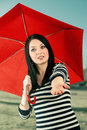 Young girl checks if it rains with a red umbrella isolated on white making Royalty Free Stock Image