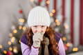 Young girl with a christmas cold and flu standing in front of the tree in warm knitted cap scarf gloves coughing Royalty Free Stock Image