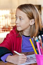 Young girl in classroom looking away colouring from camera Stock Photos
