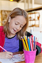 Young girl in classroom looking down colouring a or library setting Royalty Free Stock Image