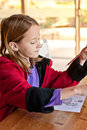 Young girl in classroom side view colouring a or library setting Royalty Free Stock Image