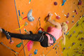 The young girl climbs the steep wall on climbing gym Stock Photography