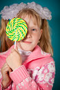 Young girl close one eye with lollipop Stock Image