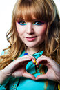 Young girl with colorful make up in love making heart symbol hands Royalty Free Stock Images