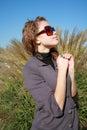 Young girl costs near a bush Stock Photos