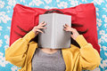 Young girl covering her face with an open book Royalty Free Stock Photo