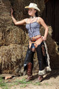 Young girl in cowboy clothes standing near the barn Royalty Free Stock Photo