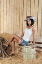 A young girl in cowboy hat sitting on a barrel in a barn with straw Stock Images